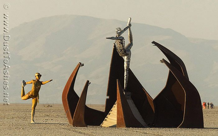 Burning Man Women Body Painting | Gold body painted woman posing next to the sculpture of Silver Man.