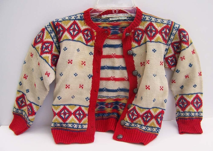 A child's hand knit Norwegian sweater with pewter buttons. The ribbon label inside reads B.K.S. Handmade in Norway Pure Wool, Richard M. Green. This sweater is at least 70 year's old, likely older.