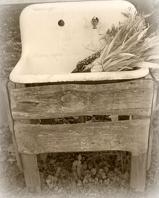 vintage cast iron wall hung sink...nice support of barnwood...have cast iron legs.