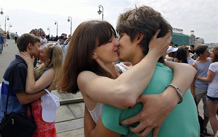 Nearly 100 Russian couples embraced and locked lips during an 'International Kissing Day' event in Moscow on July 6, 2012.
