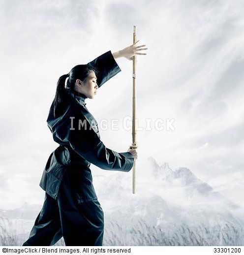 RF 33301200 Portrait of a young woman holding a wooden stick standing in a martial arts stance :: ImageClick
