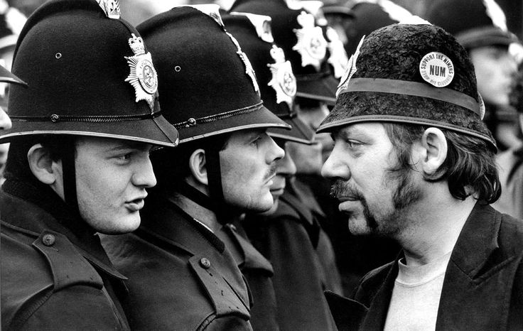 Striking miner, George 'Geordie' Brealey, confronts a line of police officers while wearing a toy helmet at Orgreave coaking plant near Rotherham, Yorkshire. The subsequent outbreak of violence between police and pickets, known as the 'battle of Orgreave', was one of the most bloody and controversial of the 1984-85 miner's strike Photograph: Don McPhee