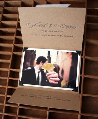 Lovely Kraft paper and calligraphy invites, adore the photo corners used to hold a photo of the couple inside the card.