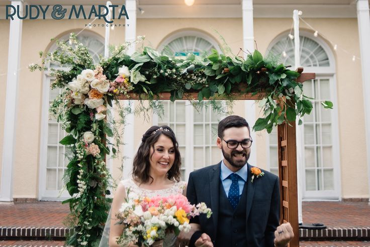 YES!!! the new mr. & mrs. head down the aisle under  an arbor of lemon leaf, seeded eucalyptus & fern garland with white and peach roses, white lisianthus, button chamomile, pink larkspur, white spirea & peach stock peppered throughout.