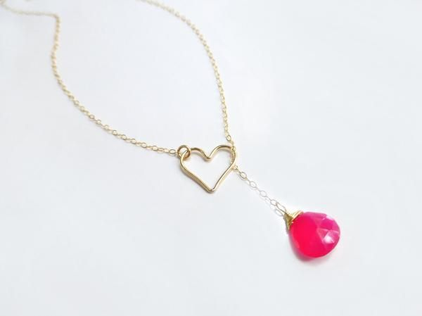 Will you be my love? Fall in love with this delicate, sweet lariat. Adorned with a vibrant hot pink gemstone, this necklace has a subtle shimmer and distinctive
