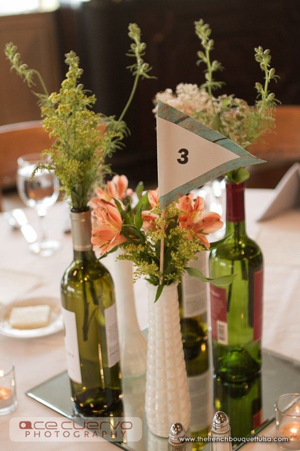 Peach flowers and greenery in milk glass vases and wine Wine bottle wedding centerpieces