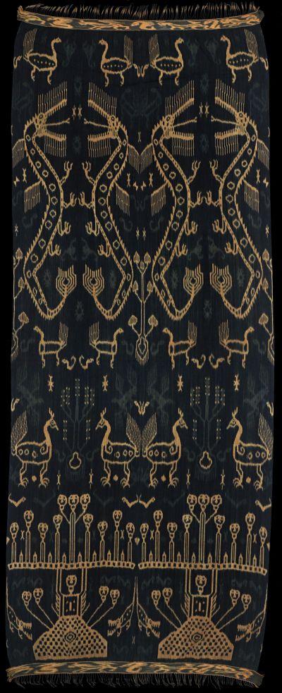 Ikat from East Sumba, IndonesiaHinggi kawuru (pahudur). 'Blue Sumba' (handspun). Named not after largest motif, but after most important: andung (skull tree). Large naga (dragons), ayam (cocks), buaya (crocodiles). Pagi-sore: top and bottom different.