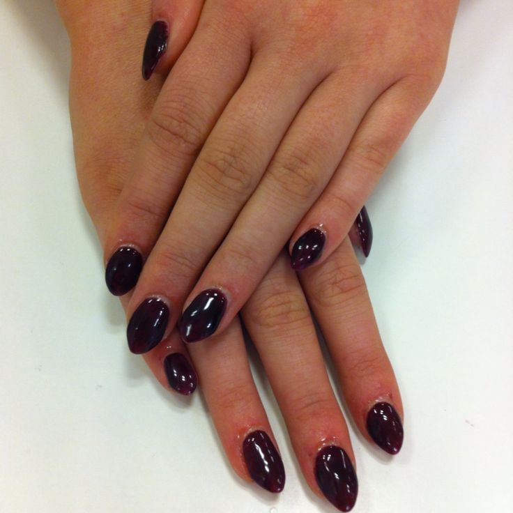 Burgundy coloured gel polish over a set of almond shaped acrylics