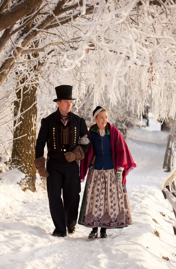 The man is wearing a bunad from Valdres. The top hat is to mark the occasion. The woman is wearing a bunad from Nord-Tröndelag, a style that was used in the beginning of the 19th century.
