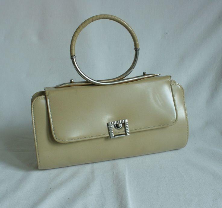 Kabelka slečny lékárníkové Extravagantní kabelka ze začátku 50. let. Je podlouhlého tvaru a má velmi zajímavě řešeno držadlo a zapínání. Barva kovových součáství je chromově stříbrná . Kabelka je ušita z imitace lakované kůže světle béžové barvy. Chlopeň kabelky je užší, než tělo kabelky. To vytváří zajímavý efekt. Vnitřní prostor je vypodšívkován ...