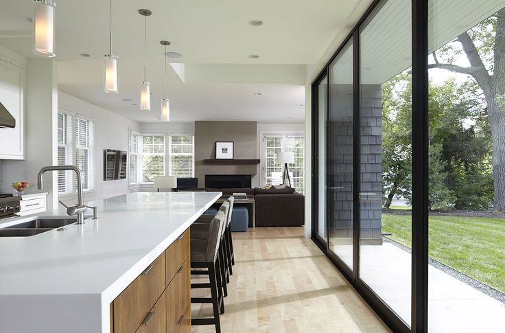 A wall of sliding doors draws light into the open white and walnut kitchen.