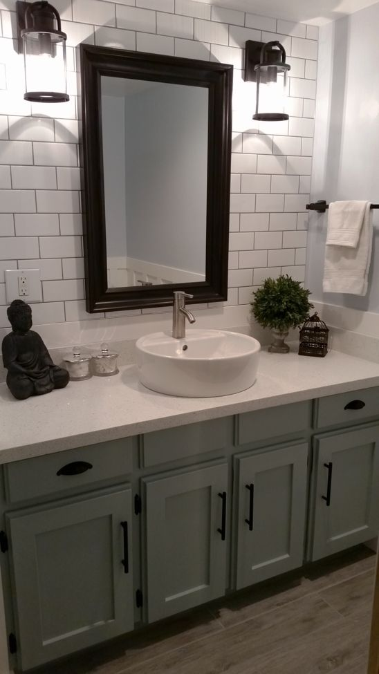 Farmhouse bathroom. blue. white subway tile backsplash. Farmhouse light fixtures. vessel sink. resurfacing cabinets. grey wood tile floor. DIY. Before and after picture.