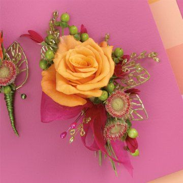 Bling bling adds a lot to a corsage, creating extra interest and sparkle. Hot pink Gerbera daisies have been trimmed closely to give an unusual accent to this orange rose.