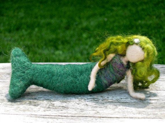 Nadel Gefilzte Mermaid Doll    Größe: 7 Zoll/17,5 cm    Mari sitzt auf den Felsen am Strand, entscheiden, welche Ozeane um weiter zu erkunden! Wo werden ihr Abenteuer sie hingebracht? Es liegt an dir zu entscheiden!    Diese Nadel Gefilzte Meerjungfrau hat eine Top, hergestellt aus einer Kombination von Grün und lila wolle, und hat einen dunklen grünen Schwanz. Mari hat lange, grüne locken mit Streifen von hellblau durchzogen, mit ein wenig weiße Wolle im Haar set aus Perlen.    Mari ist…