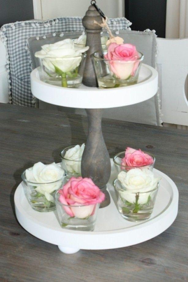 Mooi stilleven van een houten etagere met waxinelichtglaasjes met rozen