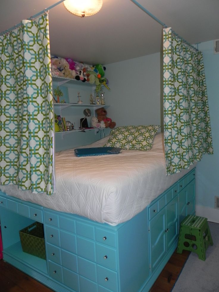 Claire's Bedroom - Repurposed Dressers used to lift bed, slats along wall hold the plywood that covers dresser to wall & hold the mattress. Curtains & pillows decorate.