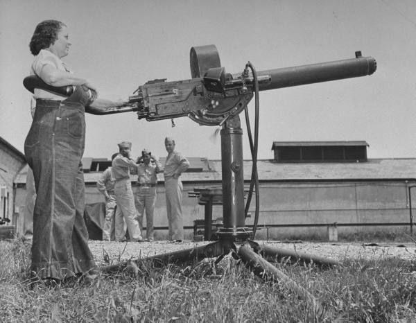 A woman fires a machine gun at Aberdeen Proving Ground.  in Aberdeen, Maryland, USA. 1942