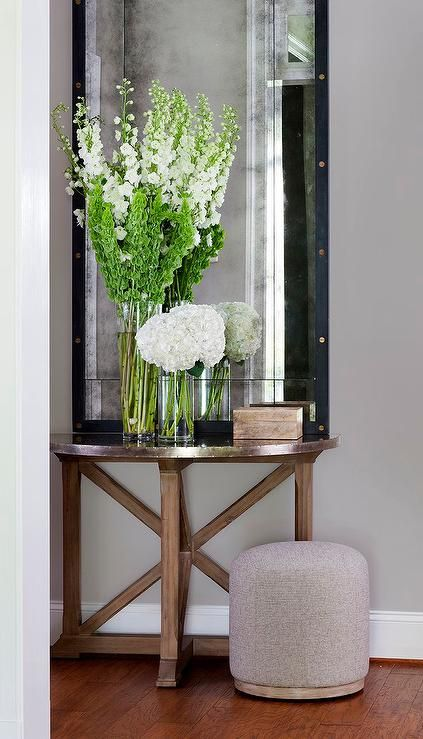 Transitional foyer boasts a wood and zinc trestle half moon table topped with fresh flowers and a tall rivets leaning mirror.