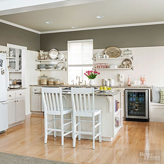 You need to check out this kitchen that was completely remodeled without breaking the bank! A refurbished, creative, cottage style kitchen replaced the typical suburban space that was in the house before. Creamy white, taupe, and khaki colors complement seasonal accessories, and the island and countertops were expanded for more workspace. Plus, look at that amazing open shelving!
