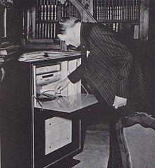 René Coty devant un meuble de palissandre, combiné radio-électrophone, dans un salon de l'Elysée, en 1955. -  Coty abandonne  ses fonctions le 8 février 1959 et devient membre de droit du Conseil constitutionnel.. - Fonctions: *Membre du Conseil constitutionnel français (5 mars 1959-22 nov 1962, président: Léon Noël. * 17° président de la République française: 16 janv 1954-8 janv 1959 (4 ans, 11 mois et 23 jours), prédécesseur: Vincent Auriol, successeur: Charles de Gaulle (V° République).