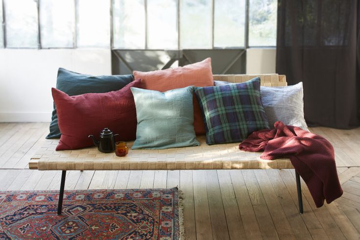 Banc en bois avec coussins aux couleurs riches et colorées.