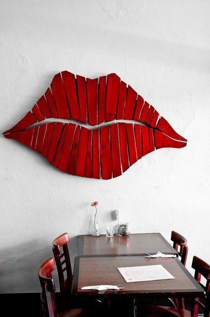 Sur le mur de la salle à dîner, pour un tête-à-tête romantique ou pas, des lèvres pulpeuses… faites en bois.