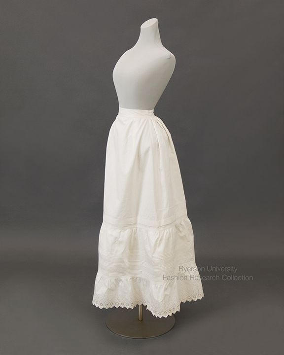 This petticoat has a story! White treated cotton petticoat, cambric lining, lace hem and horizontal pin-tucks, gathered waist, button closure, concealed front pocket in right seam, embroidered name of owner, E.L. Hughes. c.1890. FRC1986.09.101