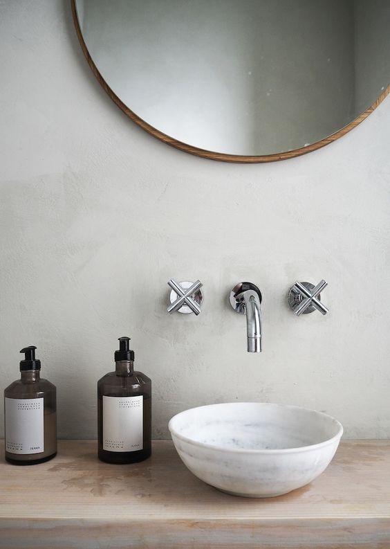 A beautiful neutral bathroom with a round wooden mirror by Frama Copenhagen