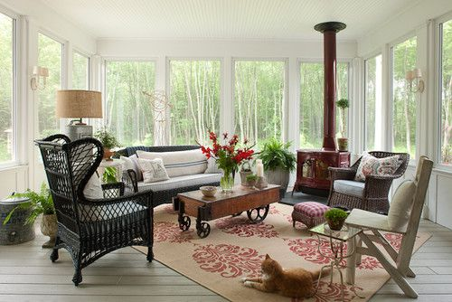 Screened in porch with a wood stove for chilly nights at this Michigan lake home.