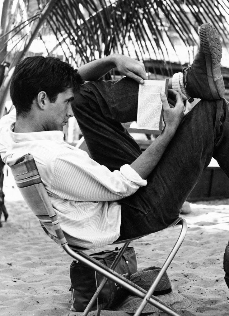 Anthony Perkins having a rest reading on the film set of 'This Angry Age', 1957.