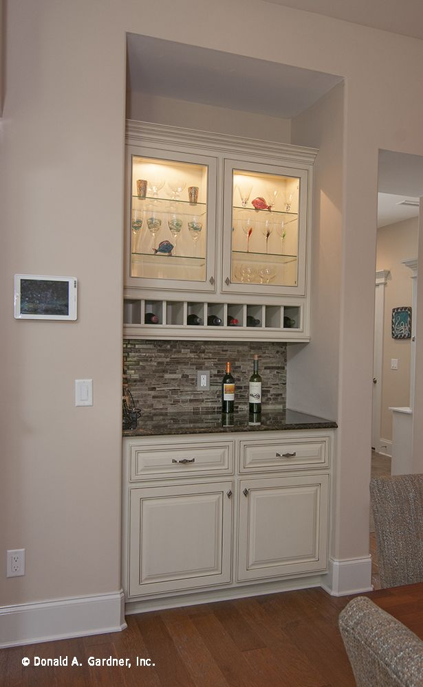 A wet bar is conveniently located by the kitchen, and features glass front cabinetry and wine bottle storage. http://www.dongardner.com/plan_details.aspx?pid=3676. #WetBar #Kitchen #Design