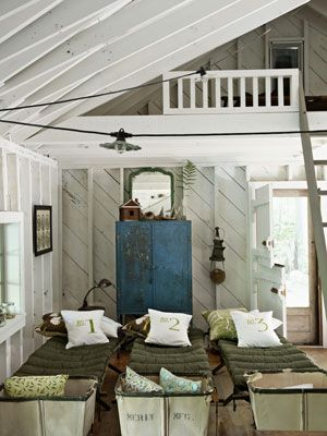 Kids Room Ideas –  Rustic Room:  A row of antique wood cots and vintage hampers fill this kids' cabin with plenty of opportunities and room to host sleepovers for friends. Canvas number-print pillows were handmade.   – Design and Decorating Ideas for Kids Rooms - Country Living