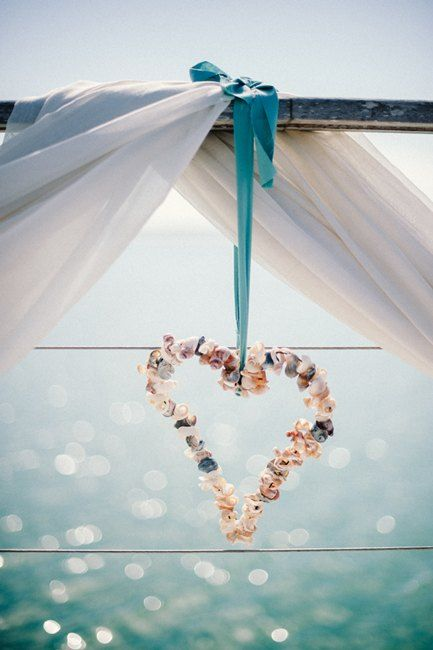 Sweet beach wedding outdoor decor. Seashells heart with ribbon. LOVE!