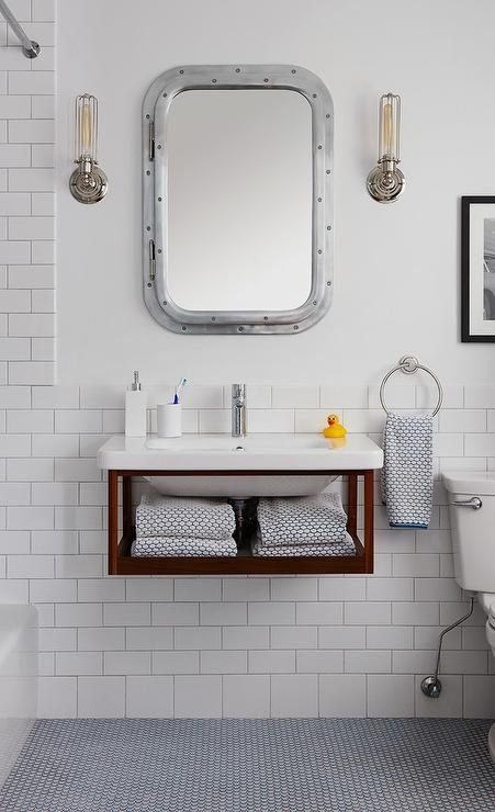 Boasting floors covered in blue penny tiles, this cottage kid's bathroom features a floating wood washstand finished with a towel shelf and a white porcelain sink paired with a modern polished nickel faucet positioned in front of white subway backsplash tiles beneath a Restoration Hardware Submarine Inset Medicine Cabinet flanked by Edison Caged Sconces.