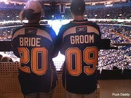 A Bride and Groom with St. Louis Blues hockey jerseys with their wedding year date. #weddings