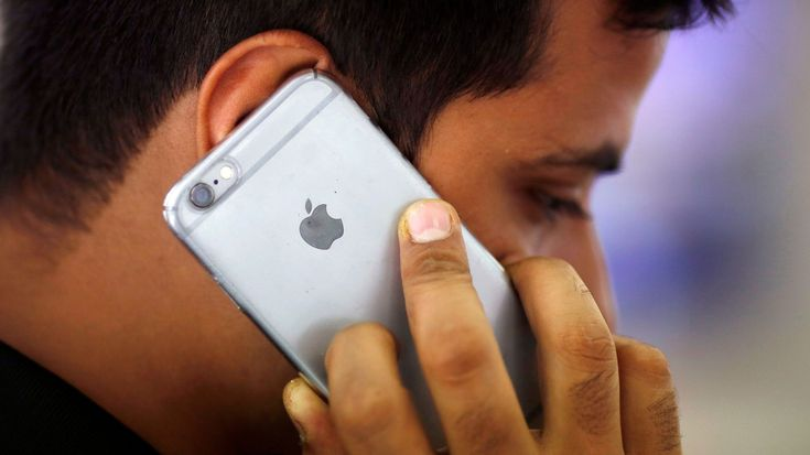 FILE PHOTO: A man talks on his iPhone at a mobile phone store in New Delhi