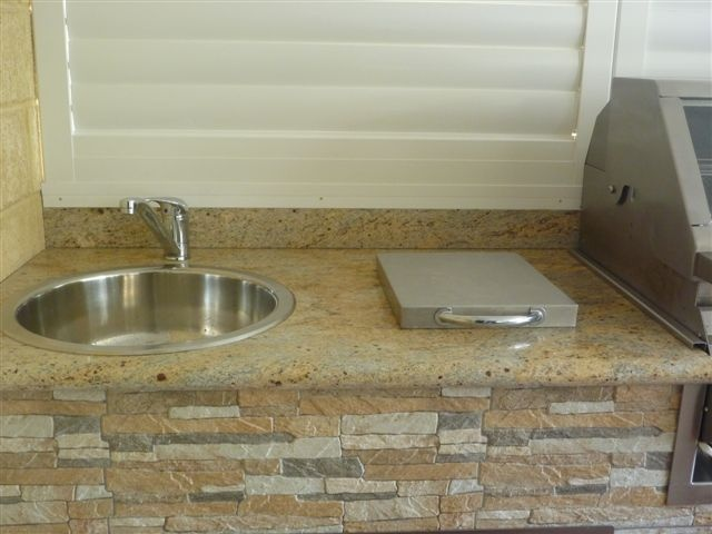 Stylish stainless steel lid covers a slide out chopping board and rubbish chute. BKCB
