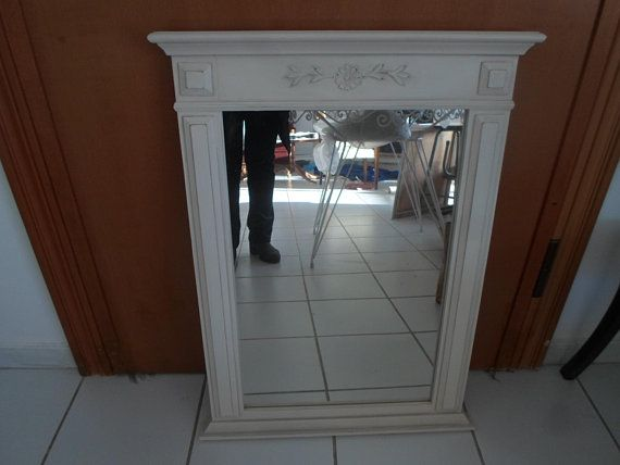 A vintage mirror solid wood painted in white creme color