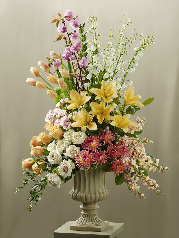 The Celebration of Love Arrangement blooms with the colours of happiness and grace to celebrate your wedding day. Peach tulips, peach roses, white roses, peach stocks, dark pink dahlias, white delphiniums, pink spray roses, peach asiatic lilies, pink flowering branches and an assortment of fresh, lush greens are beautifully arranged in a resin urn and displayed on a 3-inch pedestal to brighten the alter during your ceremony. Approx. 48