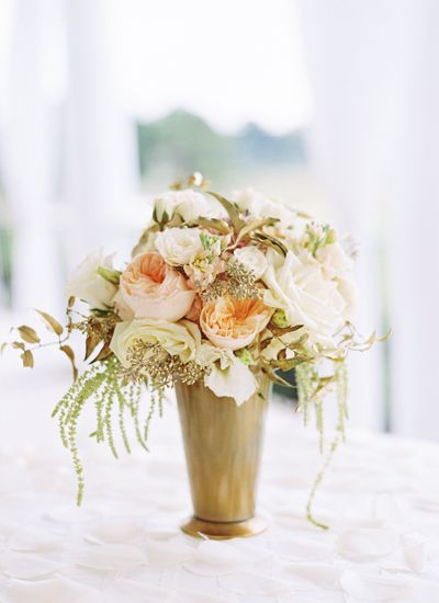 A gold mint-julep vase with peach and white flowers make a glamourous centerpiece   Landon Jacob