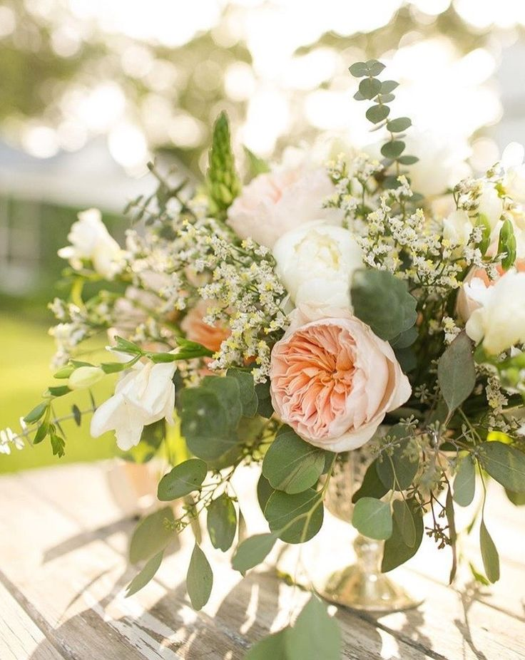 Some of the centerpieces will be gold compote vase filled with a naturally-shaped arrangement of white hydrangeas, blush spray roses, peach ranunculus, peach tulips, silver dollar eucalyptus, and gardenia foliage surrounded by gold ribbed votives.