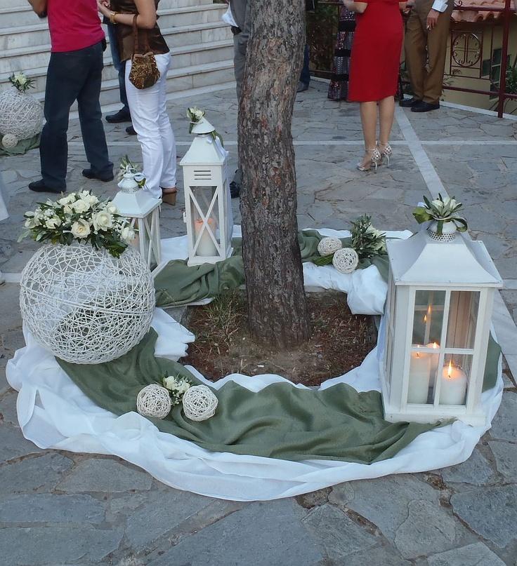Εξωτερικός στολισμός εκκλησίας με λαδί και λευκά υφάσματα, και πάνω τους λευκά φαναράκια και μπάλες μπαμπού με συνθέσεις από φρέσκια λουλούδια σε λευκό.