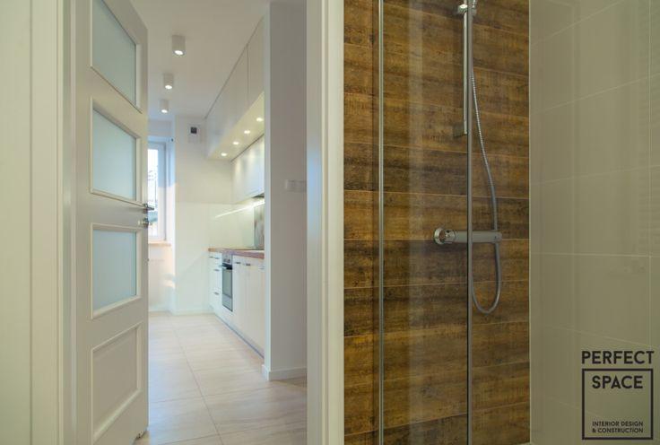 Prysznic w łazience ze szklanymi drzwiami oraz drewnianą ścianą.