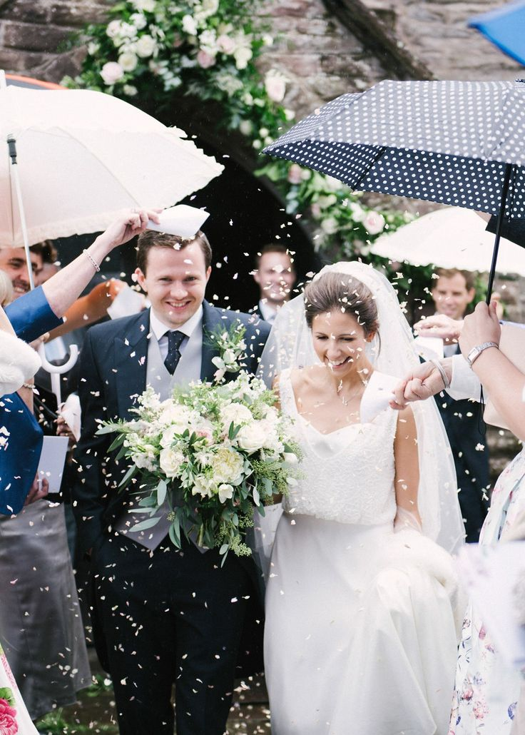 The guests create an arch of umbrellas to keep the bride and groom dry. Photography by Hannah Duffy
