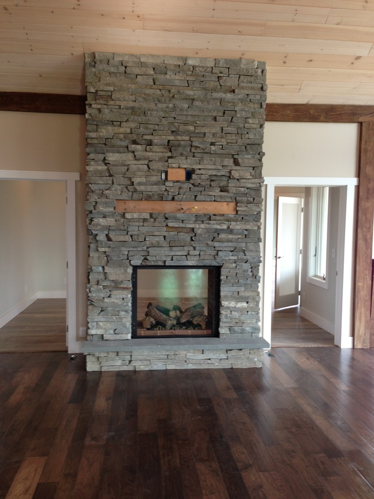stone see-through fire place with tv hanging above looking from the living room to a large foryer