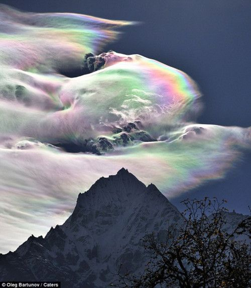 An Iridescent (Rainbow) Cloud in Himalaya  The phenomenon was observed early morning on October 18, 2009 on the path to Lamjung in the Himalayas. The mountain pictured is Thamserku.
