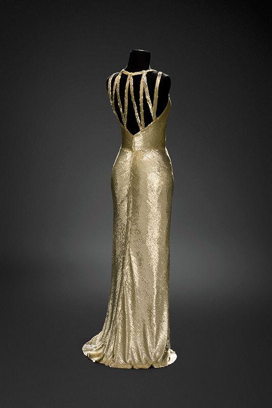Gabrielle Chanel, robe de soir 1930-1931 Fourreau Chanel fait de paillettes nacrées brodées sur tulle. Décolleté profond dans le dos, soutenu par un jeu de bretelles étroites. La jupe est formée de deux panneaux s'ouvrant sur une petite fente arrondie devant et formant une petite traîne à l'arrière.   Musée du Costume et de la Dentelle :Mode au XXe siècle