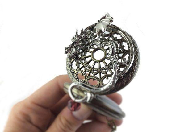 Dragon Pocket Watch Necklace dispose dune montre de poche de dragon steampunk stylisé avec une chaîne de longueur personnalisée, ou aucune chaîne de votre choix à tous. La montre de poche est une véritable travail horloge à quartz qui peut être réglée à nimporte quel fuseau horaire en tournant simplement la buse sur le dessus de la montre. Le collier du dragon fait partie de ma collection de bijoux médaillon locket unique dessins dans nombreuses formes, couleurs et motifs sur le thème. La…