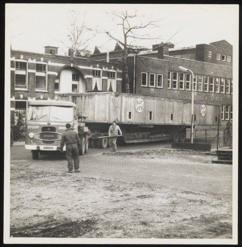 DiMCoN | Digitale Museale Collectie Nederland - Een grote kist wordt vanaf de Rotterdamse haven vervoerd naar de Phoenix Brouwerij. Hier slaat de vrachtwagen waarop de kist ligt de hoek om van de Van Asch van Wijckstraat naar het Smallepad. Rechts (buiten beeld) bevond zich de Phoenix Brouwerij.