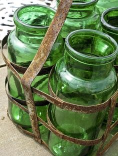 Four Green Glass Bottles in a Metal Carrier ....